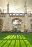 Architecture in Cambridge University, England. Kings College wall with window casting beautiful sunlight royalty free stock image