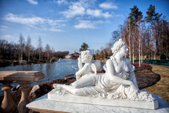 Architecture of the city. A monument, a woman and an angel on the lake Stock Photos