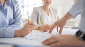 Close up of architects with blueprint at office royalty free stock photography