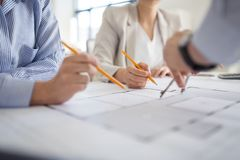 Close up of architects with blueprint at office royalty free stock images