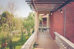 Architecture de voie ou de passage couvert sur le deuxième étage de vieux immeubles de brique de vintage près de jardin extérieur image libre de droits
