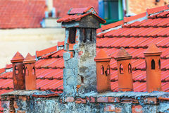 Architecture details of the house with old chimneys and tile roof on the background Stock Photography