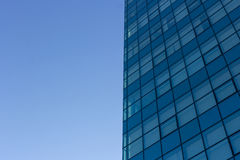 Architecture details of modern building with glass facade on blue sky background. Royalty Free Stock Image