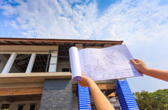Architecture drawings in hand on big house building Royalty Free Stock Photos