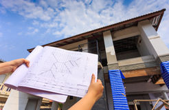 Architecture drawings in hand on big house building Royalty Free Stock Photography