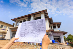 Architecture drawings in hand on big house building Royalty Free Stock Images