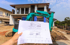 Architecture drawings in hand on big house building Stock Photo