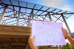Architecture drawings in hand on house building Royalty Free Stock Image