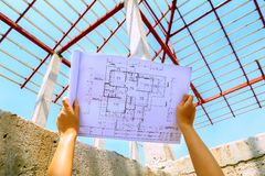 Architecture drawings in hand on house building Royalty Free Stock Photography