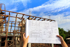 Architecture drawings in hand on house building ba Royalty Free Stock Image