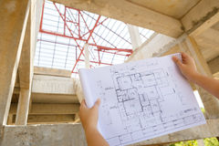 Architecture drawings in hand on house building background Stock Photos