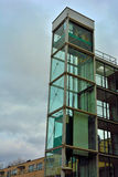 Architecture, glass elevator shaft. Architecture, beautiful  glass elevator shaft in a clouded sky Stock Image