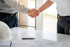 Architecture and home renovation concept - builder with blueprint shaking partner hand in retro style.  royalty free stock images