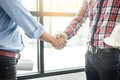 Architecture and home renovation concept - builder with blueprint shaking partner hand.  stock photos