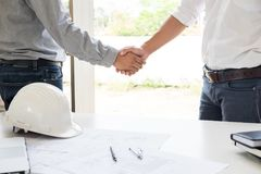 Architecture and home renovation concept - builder with blueprint shaking partner hand in retro style.  royalty free stock image