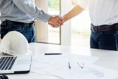 Architecture and home renovation concept - builder with blueprint shaking partner hand in retro style.  stock photo