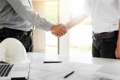 Architecture and home renovation concept - builder with blueprint shaking partner hand in retro style.  stock image