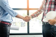 Architecture and home renovation concept - builder with blueprint shaking partner hand.  royalty free stock photography
