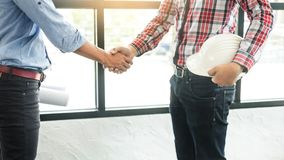Architecture and home renovation concept - builder with blueprint shaking partner hand.  stock photo