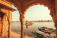 Architecture in indian traditions and people relaxing around the lake boats. JAISALMER, INDIA - FEB 2: Architecture in indian traditions and people relaxing royalty free stock images