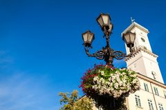Architecture of Lviv streets on blue sky background. Lamp with flowers. Architecture of Lviv streets on blue sky background. Lamp with flowers Town Hall tower royalty free stock photo
