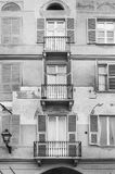 Italian balcony in Cuneo. Architecture of the Medieval Piedmont City of Cuneo in Italy. Vintage Italian balcony in Mediterranean style. Black and white picture Royalty Free Stock Images