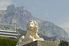 Architecture and mountains. This marble lion sculpture is situated in Vorontsov Palace - Alupka, Crimea. The lion is situated against the famous Ay-Petry stock photography