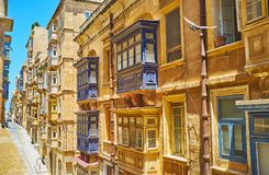Architecture of old Valletta, Malta. The dense buildings along St Dominic street with typical wooden Maltese balconies - the visit card of local architecture Stock Image