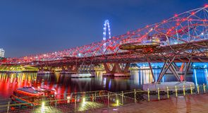 Singapore Jetty Bayfront. Architecture of pedestrian bridge, ferris wheel in the background illuminated at dusk. Cruise docked at North Jetty Bayfront in Marina Royalty Free Stock Photos