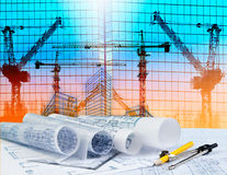 Architecture plan on architect working table with building and r. Eflection of crane construction on mirror building Stock Images