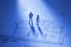 Architecture House Home Plans People. To miniature figures standing on a house blueprint as if discussing the plans Stock Images