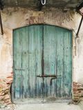 Architecture. Rural buildings. Details. Green colored old door, shaped arched and made with two woody hinged doors closed by a sturdy iron bolt Royalty Free Stock Photography