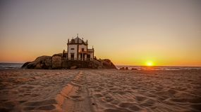 Capela do Senhor da Pedra in Miramar near Porto is a turistic spot built on the beach with awesome portuguese sea sunset royalty free stock image