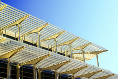 Architecture with sun blinds. Unusual sun blinds at the side of an office building against clear blue sky stock photos