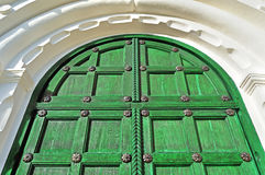 Architecture texture background. Vintage wooden bright green door with metallic rivets. And upper arch of white stone - colored architecture background Stock Photography