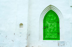 Architecture view of architecture details - old green metal forged door with arcade on the white stone wall. Royalty Free Stock Image