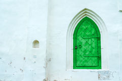 Architecture view of architecture elements - aged bright green metal forged door with arcade on the white stone wall. Royalty Free Stock Photography
