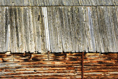 Architecture of Western Barn. Closeup of log barn shows notched and fitted logs.  Roof line is layered weatherd boards Stock Photography