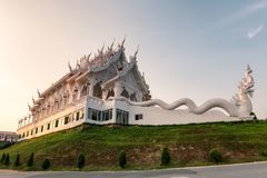 Architecture white church with dragon statue on hill in evening at Wat Huay Pla Kang. Chiang Rai stock image