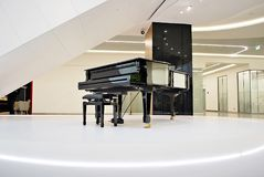 Architecture, wide hall with grand piano, interior. Grand piano for everyone to use in hall Royalty Free Stock Photos
