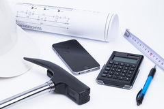 Architecture workplace. An architecture composition with helmet, hammer, calculator, cell and house plan over white royalty free stock photography