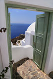 Architecturel building in Santorini with the door open to the ocean. on a sunny sommer holiday. Architecturel building in Santorini with the green door open to Stock Images