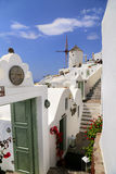 Architecturel building in Santorini with the door open and view to the beautiful buildings and a mill with a blue sky Royalty Free Stock Photography