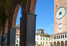 The architectures of Cremona. Italy, Cremona, Duomo Square, view of the Torrazzo bell tower basement from the Town Hall arcade Stock Photos