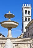 Architectures and religion in Assisi. Italy,Umbria,Assisi,the fountain and the Del Popolo tower in Municipal square Stock Photo