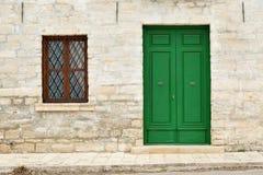 Architectuurdetails van de Renaissance - groen geschilderd houten deur en venster met een rooster van een steenhuis in Kavarna-st stock foto's