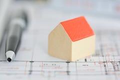 Architectuurplannen van een gebouw met klein modelhuis bovenop blauwdrukken stock foto's