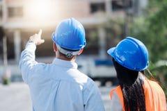 Architekci I inżynier przy budową patrzeje projekty i wskazywać obraz royalty free