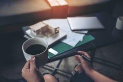 Architekci myśleć masa modela i projektuje podczas gdy pijący gorącą kawę z sklepowym rysunkowym papierem Zdjęcia Royalty Free
