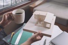 Architekci myśleć masa modela i projektuje podczas gdy pijący gorącą kawę z sklepowym rysunkowym papierem i laptopem Zdjęcia Stock
